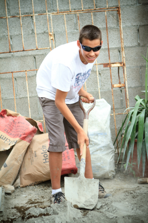 A young man wearing sunglasses smiles while he shovels dirt during a service project.
