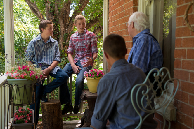 Three young men sit with an elderly man and talk with him on his porch, which is covered in potted flowers and chairs.