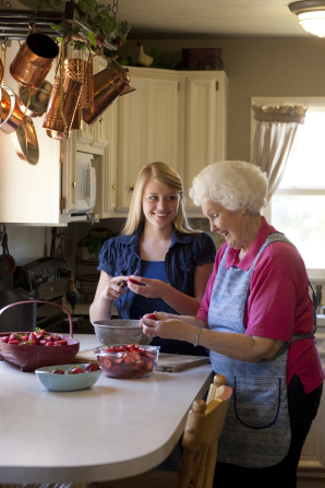 A young woman stands next to an elderly woman in her kitchen and cuts strawberries with her.