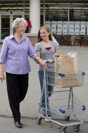 A young woman pushes a shopping cart with a brown bag full of groceries inside while an elderly woman walks beside her.