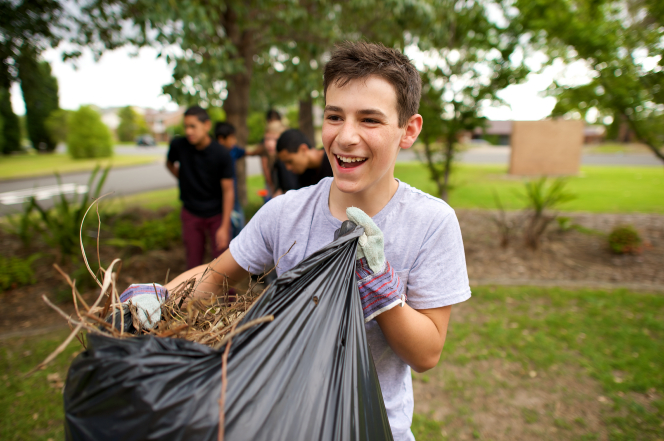 A young man wearing work gloves holds open a black garbage bag and fills it with leaves and twigs as he helps clean a yard with other young men.