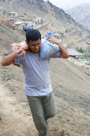 A young man carries bags of dirt to clear out a home for a service project.