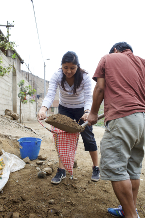 A young woman holds a bag open as a boy shovels dirt into it.