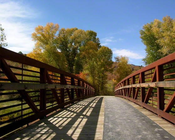 A wooden bridge leading to trees with orange, yellow, and green leaves, with a hill beyond and a blue sky overhead.