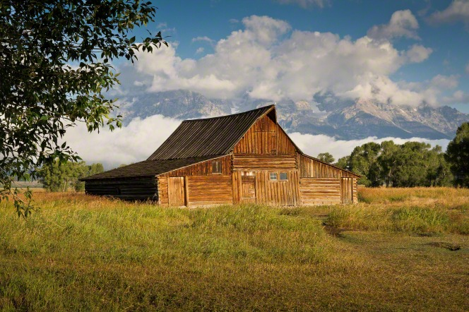 An old wooden barn in a field near trees, with mountains and clouds in the background.