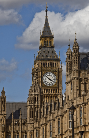 The large white clock of Big Ben, surrounded by other historic buildings in London, England.