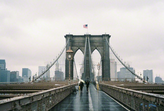 A photo of two people walking on the Brooklyn Bridge in New York City on a rainy day, with an American flag waving in the wind at the top.