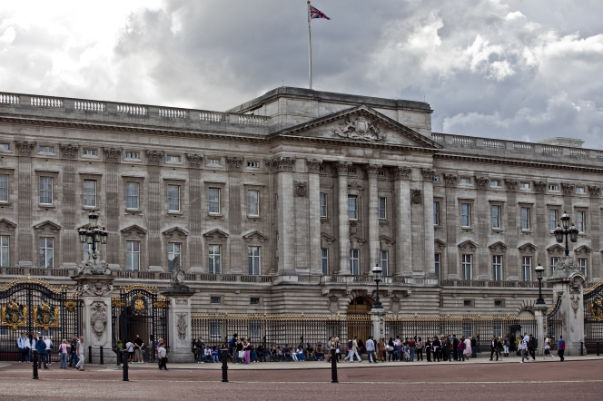 Buckingham Palace with a flag on top and people walking below on a cloudy day in London, England.