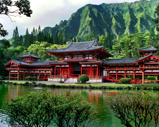 A large, white, black, and red Buddhist temple in Hawaii, seen beyond a pool of water with large green trees and mountains rising in the background.