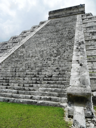 A large stone pyramid with a long row of stairs leading to the top, with a partially cloudy sky seen overhead.
