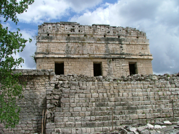 The stone wall of a ruin with three doorways at the Chichen Itza site in Mexico.