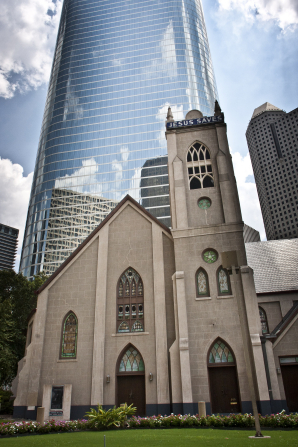 A large stone church with stained-glass windows, standing in front of a large skyscraper on a partly cloudy day.