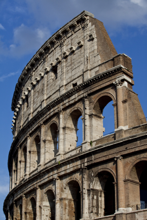 A side view of the Colosseum in Rome, Italy, with the blue sky in the background.