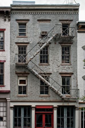 A fire escape outside a gray-brick building with many windows in Louisville, Kentucky.