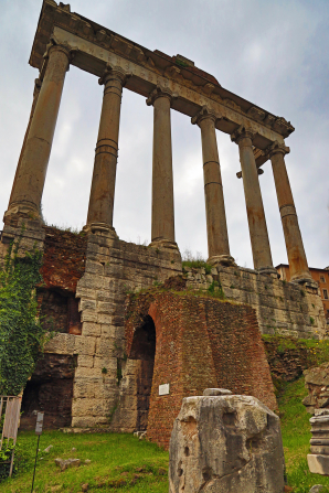 The six pillars of a forum with green vegetation below in Rome, Italy.