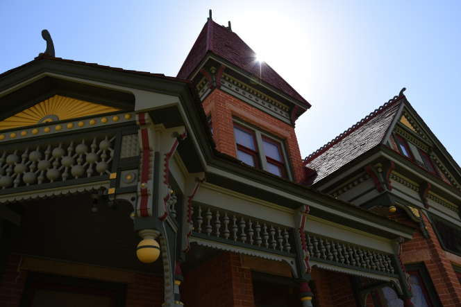 Sun shining down on the red brick and green and yellow wooden trim of the Heritage House.