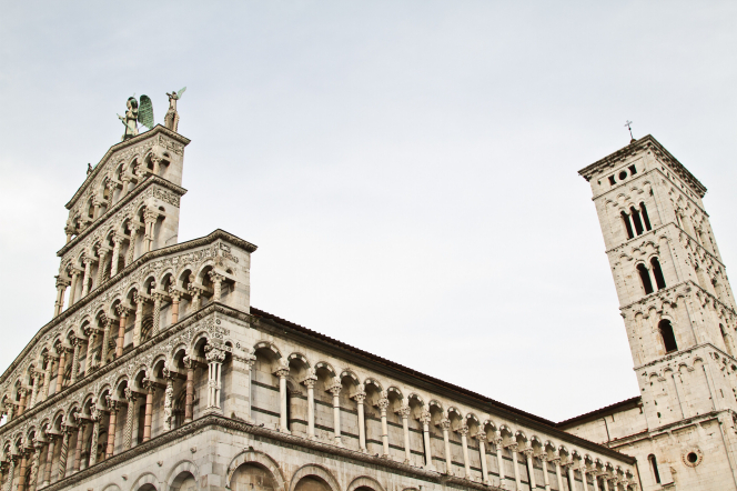 A church with many small pillars and two statues on the top in Lucca, Italy.