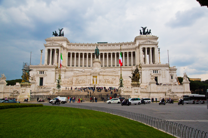A lawn, vehicles, and people outside the Victor Emmanuel monument in Rome, Italy.