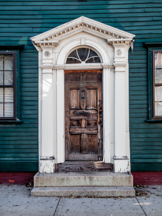 A brown, well-worn wooden door in a large, white, ornate door frame on a teal house.