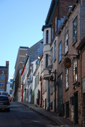 Buildings lining a street with two parked vehicles in Old Quebec, Canada.