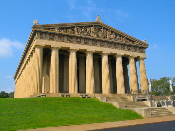 Green grass surrounds the Parthenon in Nashville, Tennessee, with its tall pillars and Greek sculptures.