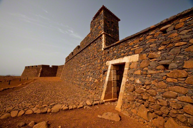 A photo of the entrance to the royal fortress of Saint Philip, made up of gray and orange stones, on Santiago Island, Cape Verde.