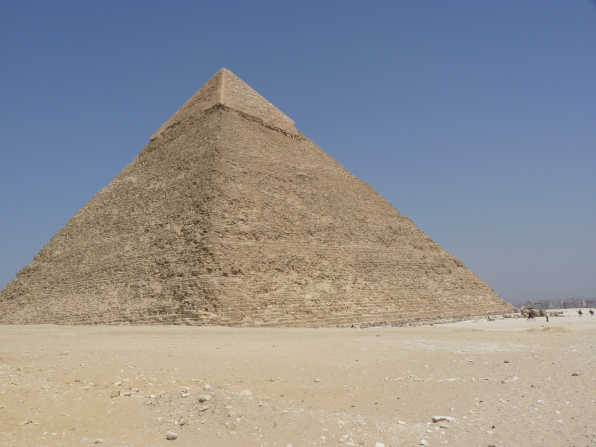 A large pyramid in Giza, Egypt, surrounded by desert, with a clear blue sky overhead.
