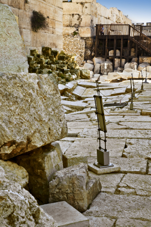 Temple ruins with stone pathways protected by a rope fence in Jerusalem.