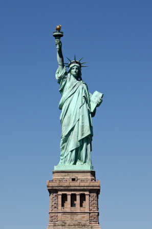 The green Statue of Liberty standing over New York Harbor, holding a torch toward a clear blue sky.
