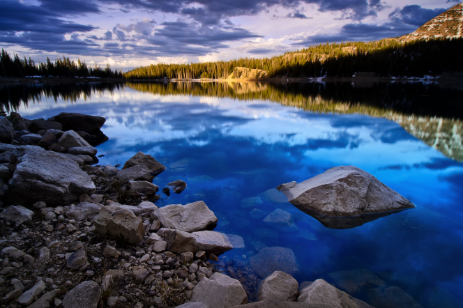 The sun rises over a lake surrounded by rocks and trees, with clouds above reflected in the water.