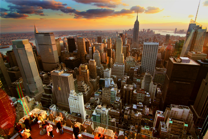 An aerial view of New York City with the sun setting in the background.