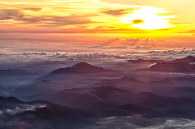 An aerial view of mountain peaks above low-lying clouds in Japan, with the sun rising in the background.