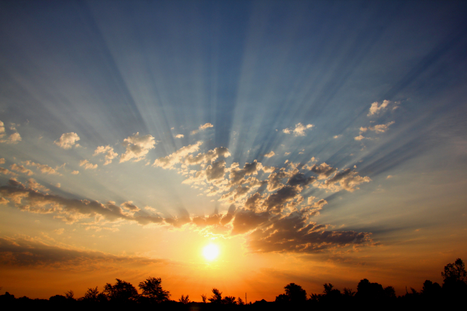 The sun rises in the sky, radiating long rays through the clouds, with trees silhouetted down below.
