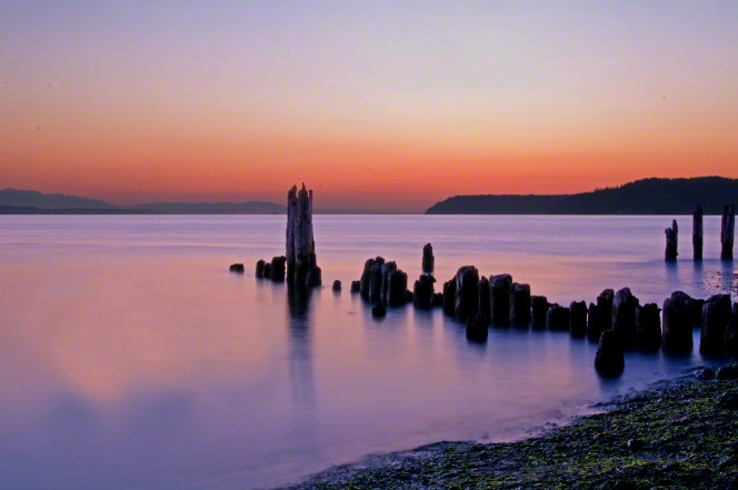 An old pier extends out into the water where purple light is reflected after the sun sets on the horizon.