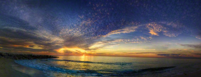 A panorama of the sun setting over the ocean, with clouds in the sky.