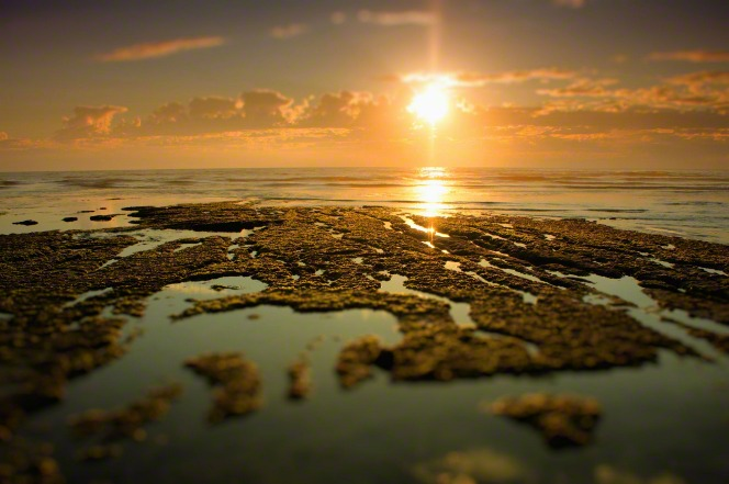 The sun sets through clouds over a tide pool.