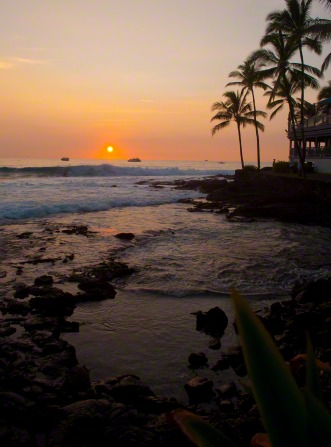 The sun sets over the ocean, with a view of palm trees on the rocky shore.