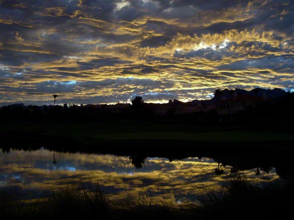 Clouds in the sky are reflected in a pond just after the sunset, with large houses and green grass in the background.