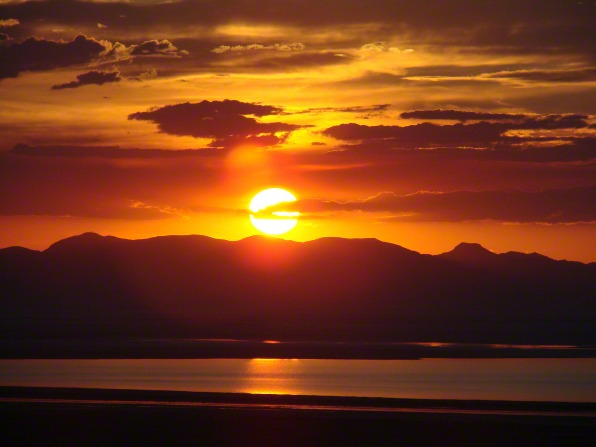 The sun sets behind mountains and clouds over the Great Salt Lake in Utah.