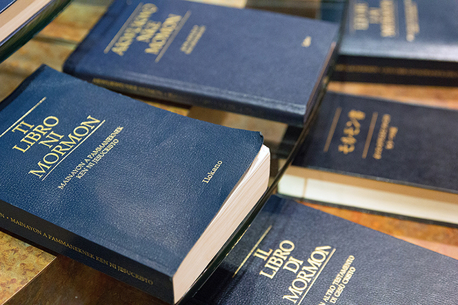 Copies of the Book of Mormon in various languages, with blue covers and gold writing, at the Independence Visitors' Center in Missouri.