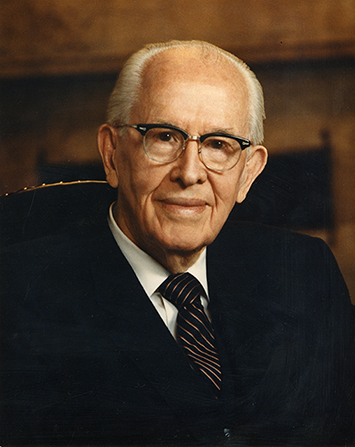 President Benson in a black suit, a white shirt, a striped tie, and glasses, smiling and sitting in a chair.