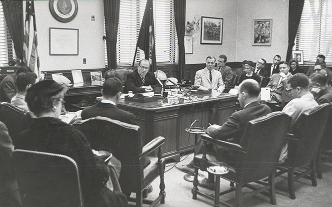 President Benson sitting behind his desk and speaking to a large group of men and a few women.