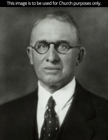 President Ezra Taft Benson's father, George Taft Benson Jr., in a white shirt, a suit, and circular glasses.