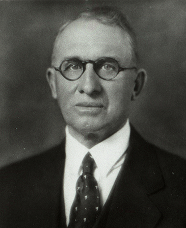 President Ezra Taft Benson's father, George Taft Benson Jr., in a white shirt, a suit, and circular glasses.