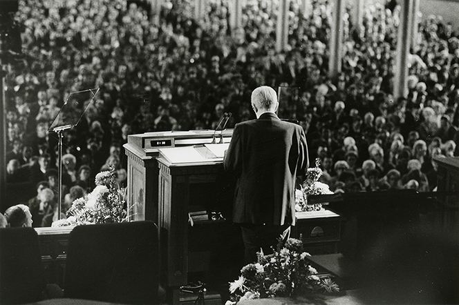 President Benson standing and speaking to a large audience from the pulpit in the Tabernacle.