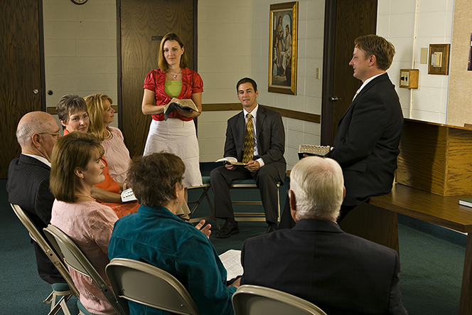 A woman standing up with her scriptures in front of other adults who are sitting in a circle in Sunday School.