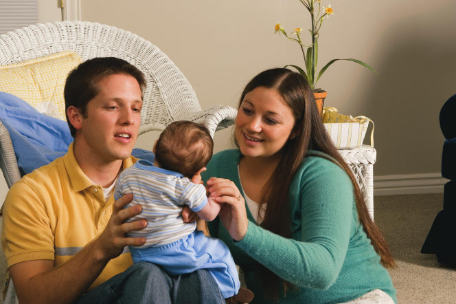 A photograph of a father and mother sitting on a living room floor and holding a baby boy.