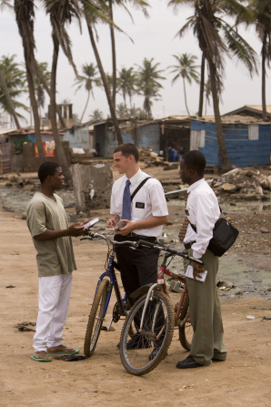 Two elders standing by their bikes and talking to a man in Ghana.