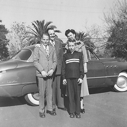 President Howard W. Hunter with his wife and two young sons, standing in front of a car.