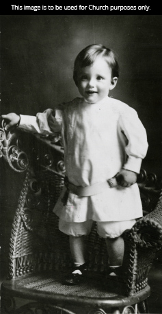 A black-and-white photograph of President Howard W. Hunter smiling and standing on a chair as a young boy.
